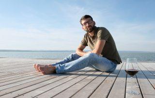 Michael Nekowitsch sitzt auf einem Holzsteg am Neusiedler See neben einem Glas Rotwein