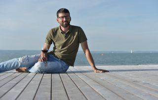 Michael Nekowitsch sitzt auf einem Holzsteg am Neusiedler See mit einem Glas Rotwein in der Hand