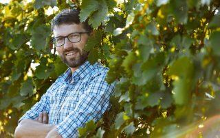 Michael Nekowitsch steht vor einer Weingartenreihe