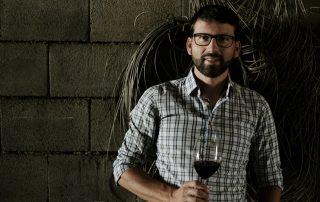 Michael Nekowitsch im Weinkeller vor einer Wand mit einem Glas Rotwein in der Hand