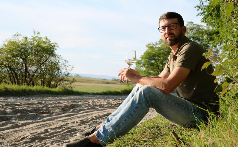 Michael Nekowitsch mit Weinglas in einer Riede in Illmitz am Boden sitzend
