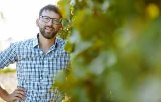 Michael Nekowitsch steht nebenr einer Weingartenreihe