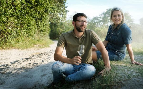 Michael und Elisabeth Nekowitsch mit Weinglas im Weingarten am Boden sitzend