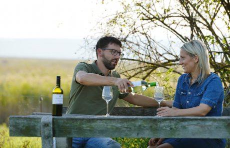 Michael und Elisabeth Nekowitsch sitzen an einem Picknickplatz und trinken Wein