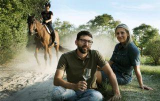 Michael und Elisabeth Nekowitsch sitzen im Gras mit Pferd und Reiterin im Hintergrund