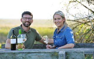 Michael und Elisabeth Nekowitsch sitzen auf einem Picknickplatz im Nationalpark Neusiedlersee mit Weingläsern in der Hand