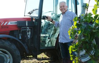 Michael Nekowitsch sen. steht vor einem Traktor im Weingarten
