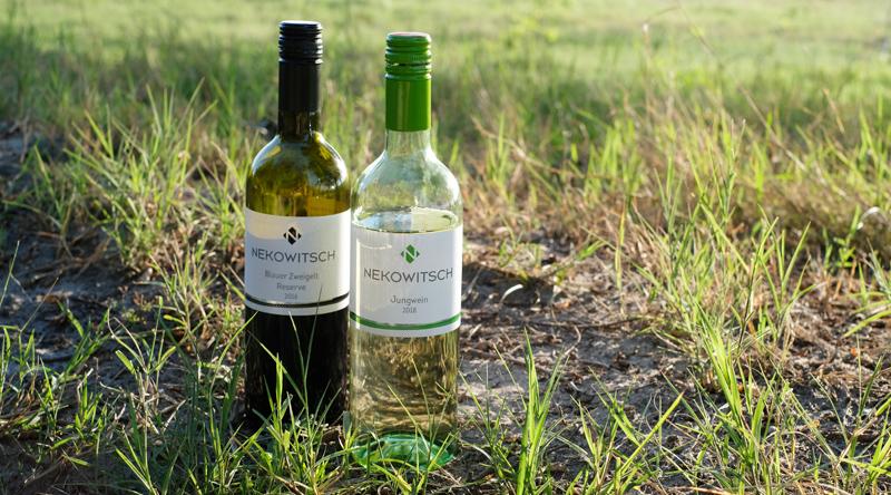Zwei Nekowitsch Weinflaschen am Boden stehend in einer Illmitzer Riede